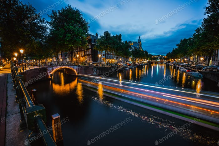 Night in Amsterdam. Lights trails and illuminated bridges on city canal at twilight. Holland