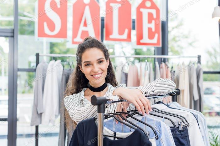 schöne shopaholic Frau, die sich im Bekleidungsgeschäft an einen Ständer stützt