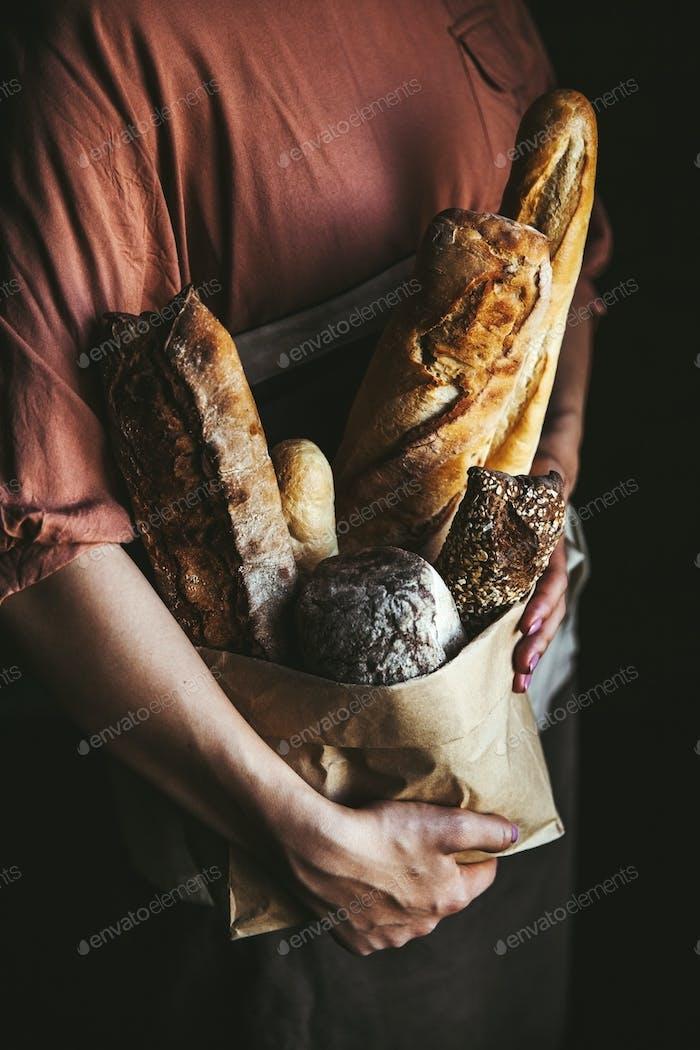 Französisch Baguettes in weiblichen Händen auf einem schwarzen Hintergrund. hausgemachtes Backen