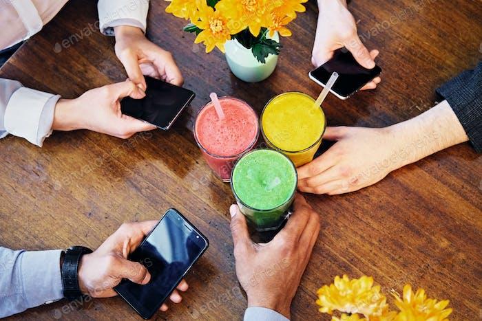 Die  Arme der Menschen, Smartphones und vegetarischer Saft.
