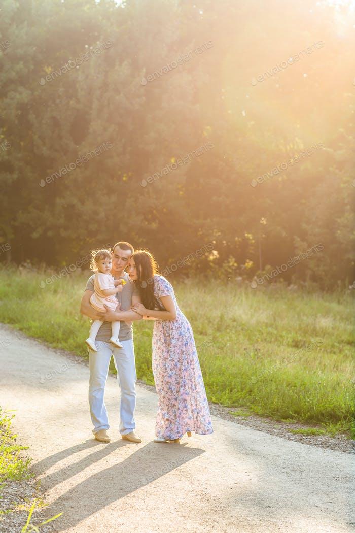 Gemischte Rennfamilie, die an einem hellen Sommertag einen ländlichen Pfad hinuntergeht.