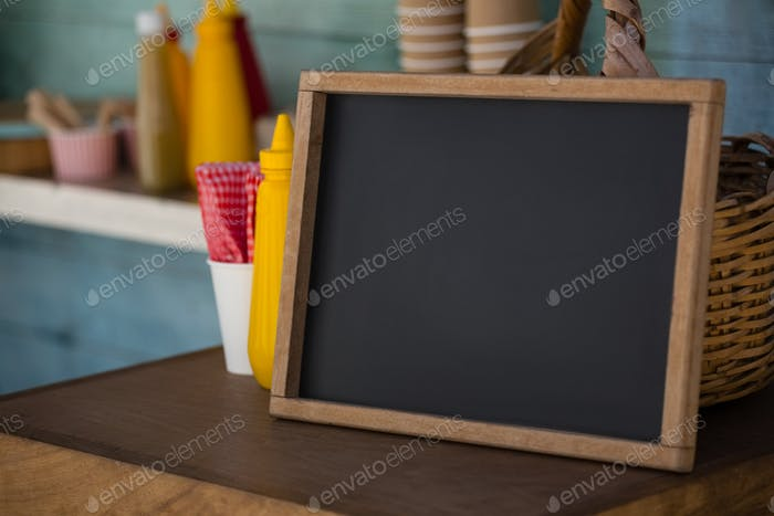 Writing slate on wooden table in food truck