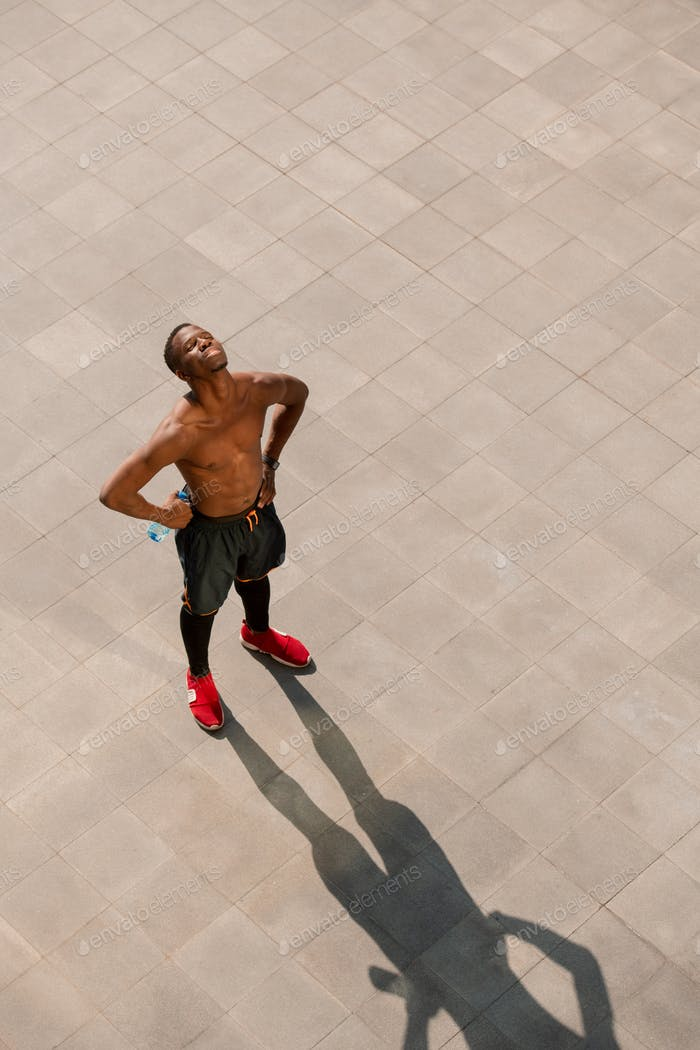 Young tired shirtless man of African ethnicity standing in urban environment