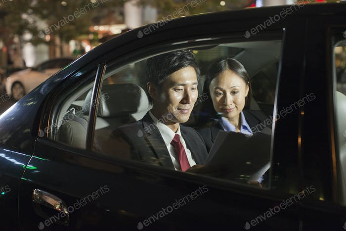 Two Business People Working In Car Back
