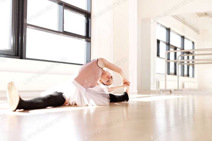 Ballet Dancer in Stretching Exercise on the Floor