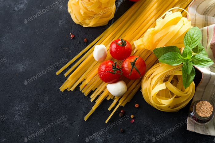 Food ingredients for Italian spaghetti on black stone slate background