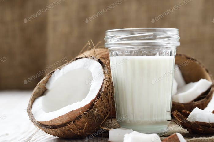 Mason jar of milk or yogurt on hemp napkin on white wooden table