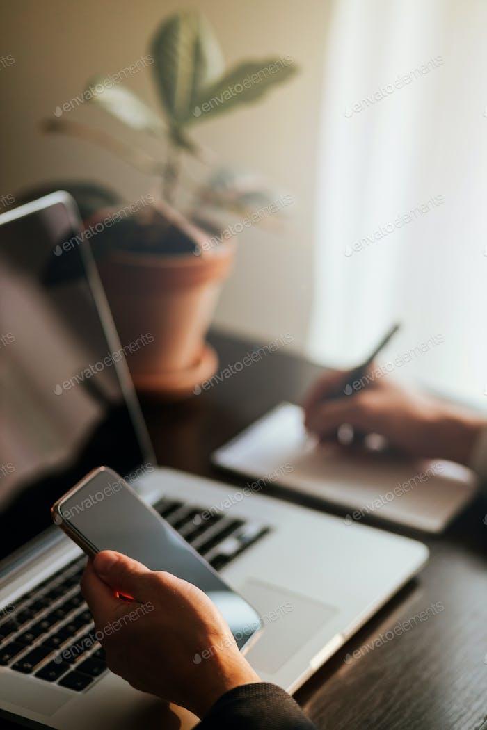 Büroangestellte Surfen Telefon und Laptop im Innenbereich