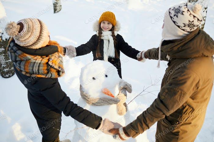 Loving Family around Snowman