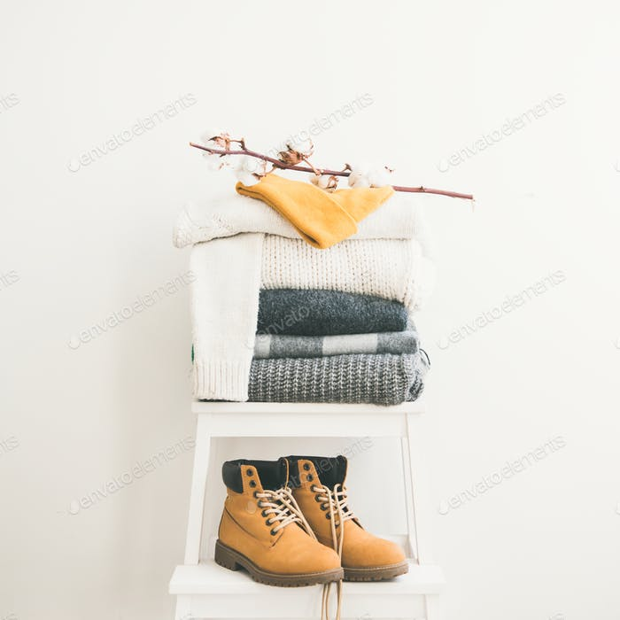 Warm clothing, blankets, boots and cap on chair, square crop