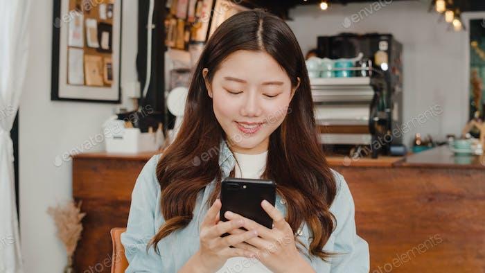 Freelance Asian women using mobile phone at cafe.