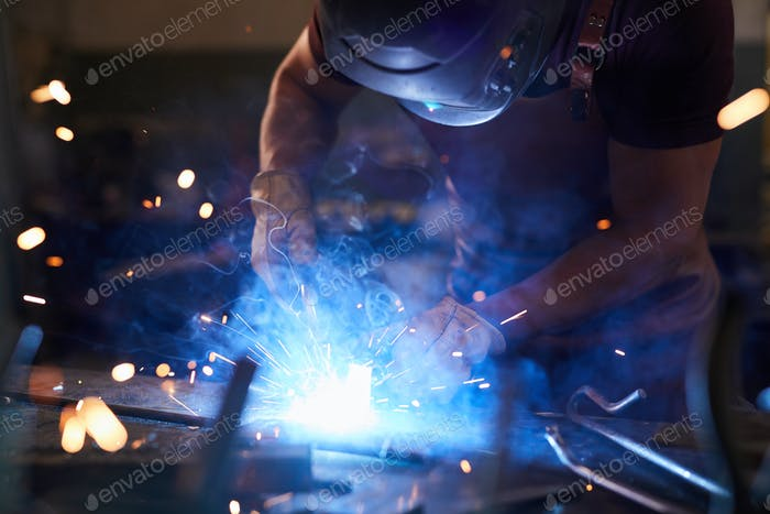 Laborer melting metal with welding tool