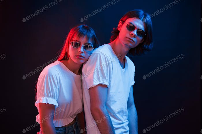 Couple standing in dark room with red and blue neon lighting