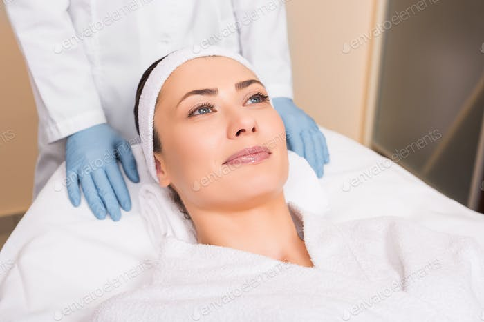 beautician standing behind woman laying at beauty salon