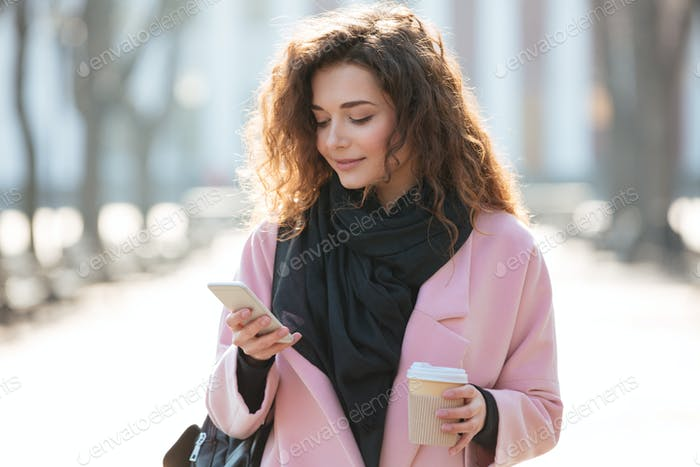 Cheerful woman walking and using her phone in the street.