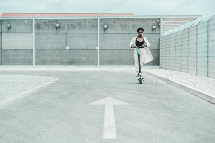 Black girl is riding an e-scooter
