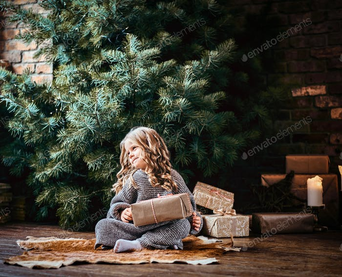 Cute little girl with blonde curly hair sitting on a floor next to the christmas tree
