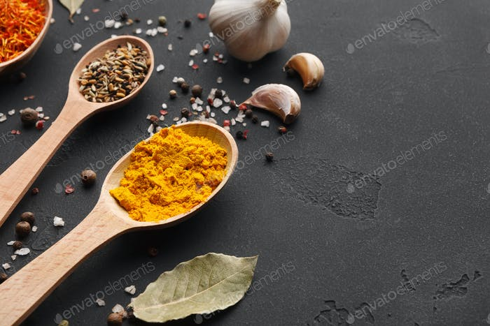 Turmeric, bay leaves and garlic on dark table