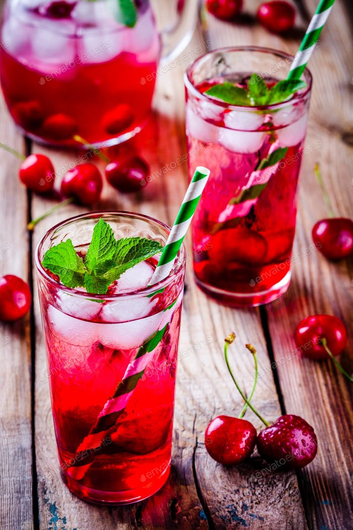 ice refreshing cherry sangria in glass with ice cubes and mint