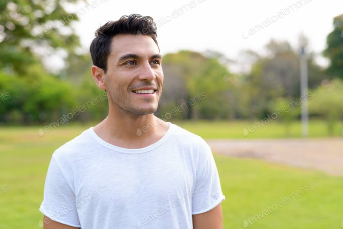 Face of happy young handsome Hispanic man thinking at the park
