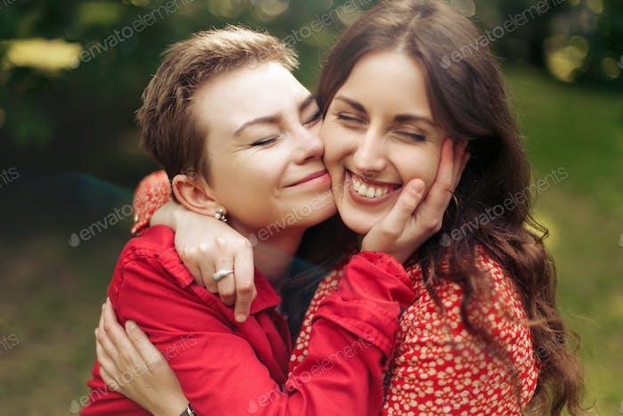 zwei stilvolle glückliche Frau umarmt und lächelnd in Europa Stadtpark, aufrichtige Momente Freundschaft Konzept