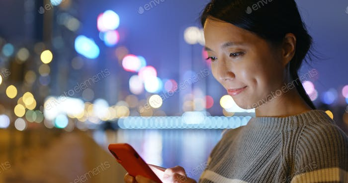 Woman work on mobile phone in city at night