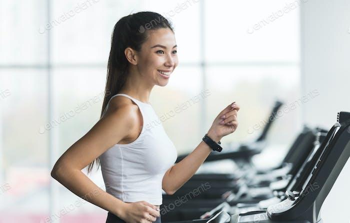 Running on treadmill. Asian woman doing cardio training