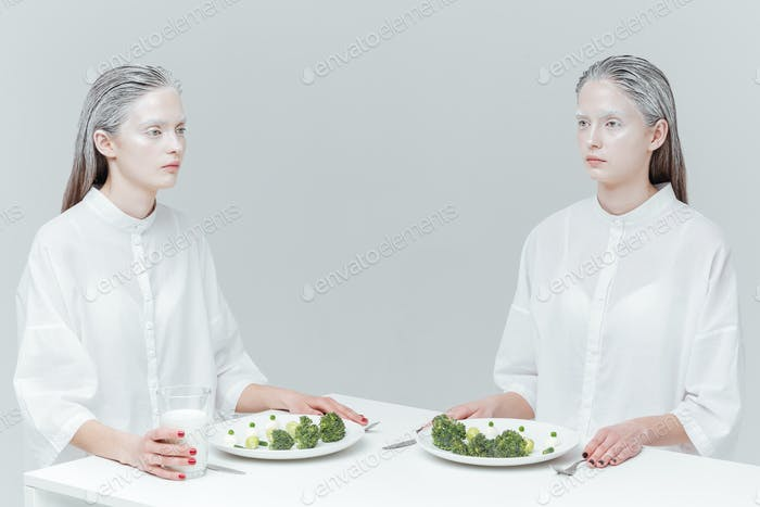 Two pretty fashion women eating at the table