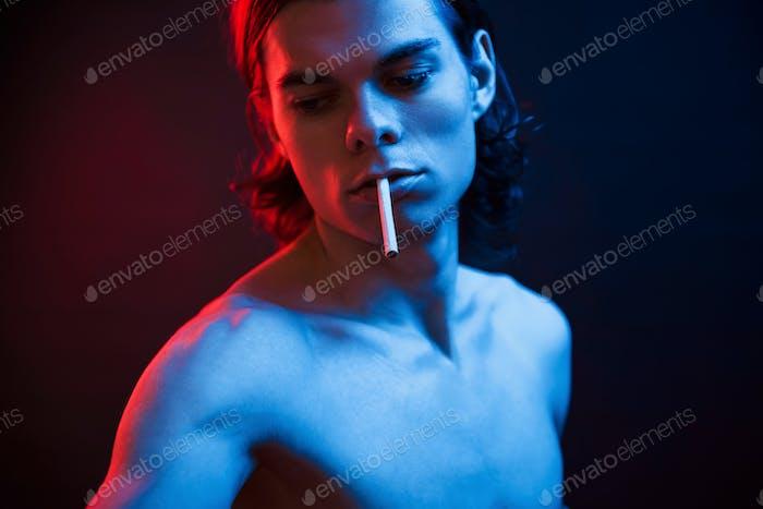 Be cool. Studio shot in dark studio with neon light. Portrait of serious man