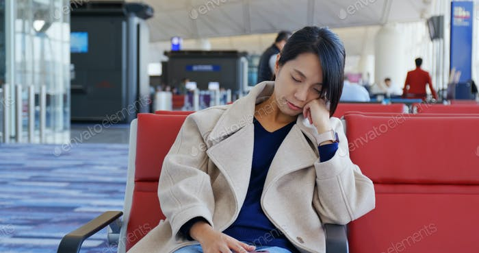 Woman sleep and sit on the check in area in the airport