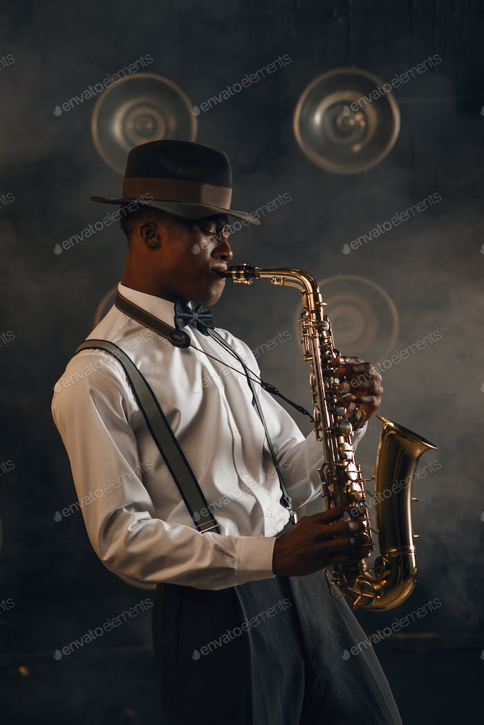 Black jazzman plays the saxophone on stage