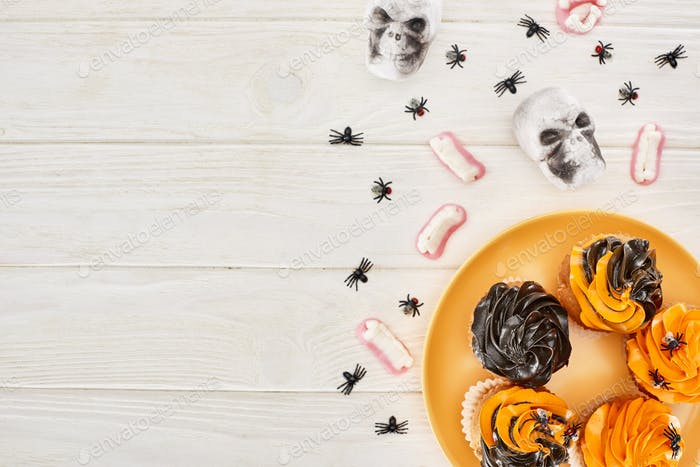 Cupcakes on Orange Plate, Gummy Teeth, Skulls And Spiders on White Wooden Table, Halloween Treat