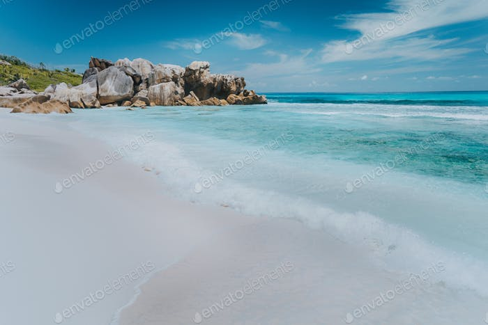 Wave on pristine blue color lagoon with granite rocks on Anse Coco beach, La Digue Island