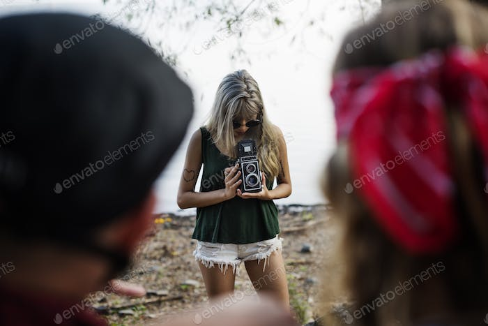 Woman Taking Friends Photo by Retro Camera on Road Trip