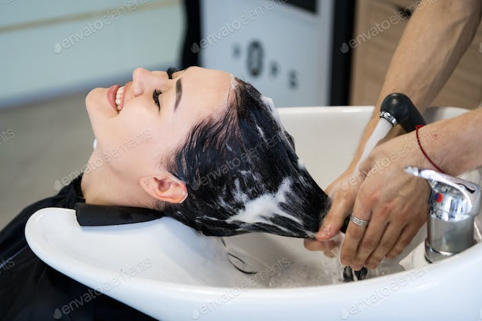 Haircare procedure in beauty salon. Hairdresser is brushing woman's hair spreading a treatment