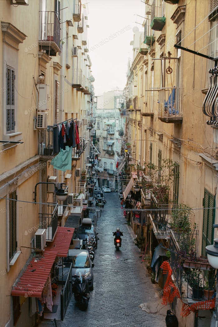 Alleyway with motorbike driving among old houses in Naples, Italy