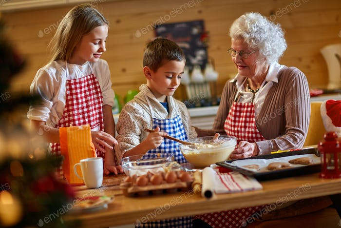 grandmother enjoying with children making Christmas cookies