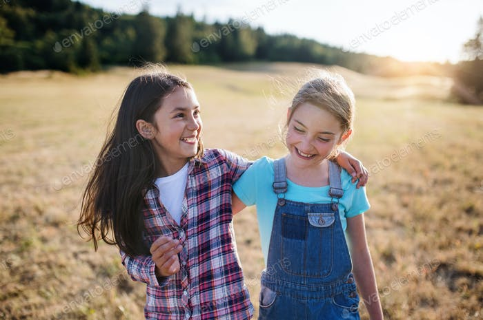 Two school children walking on field trip in nature, laughing