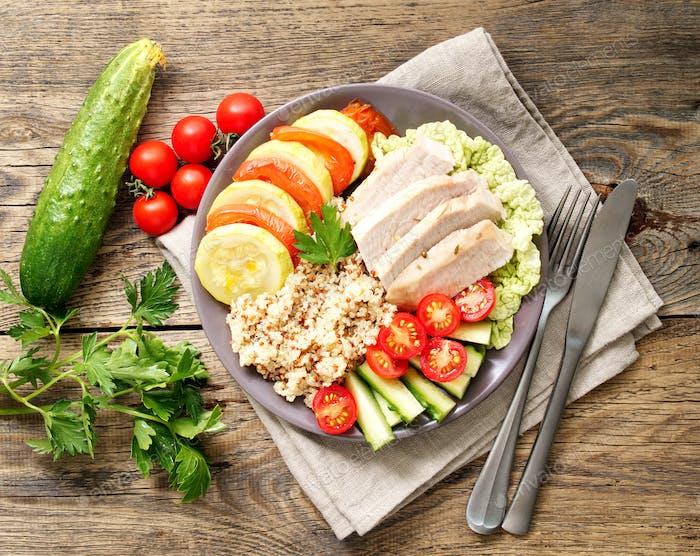Gesundes Gemüse Buddha Schüssel Mittagessen mit Truthahn, Gemüse und Quinoa auf braunem Holzrücken