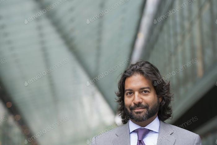 Деловой человек в деловом костюме с полной бородой и вьющимися волосами.