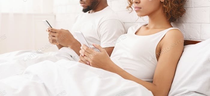 African couple in quarrel, using cellphones in bed