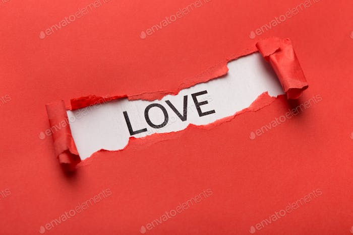 Love word bursting out from torn red paper