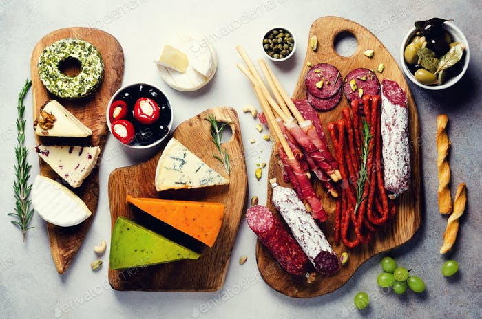 Cutting board with cold smoked meat, prosciutto, salami, assortment of cheeses, bread sticks, capers
