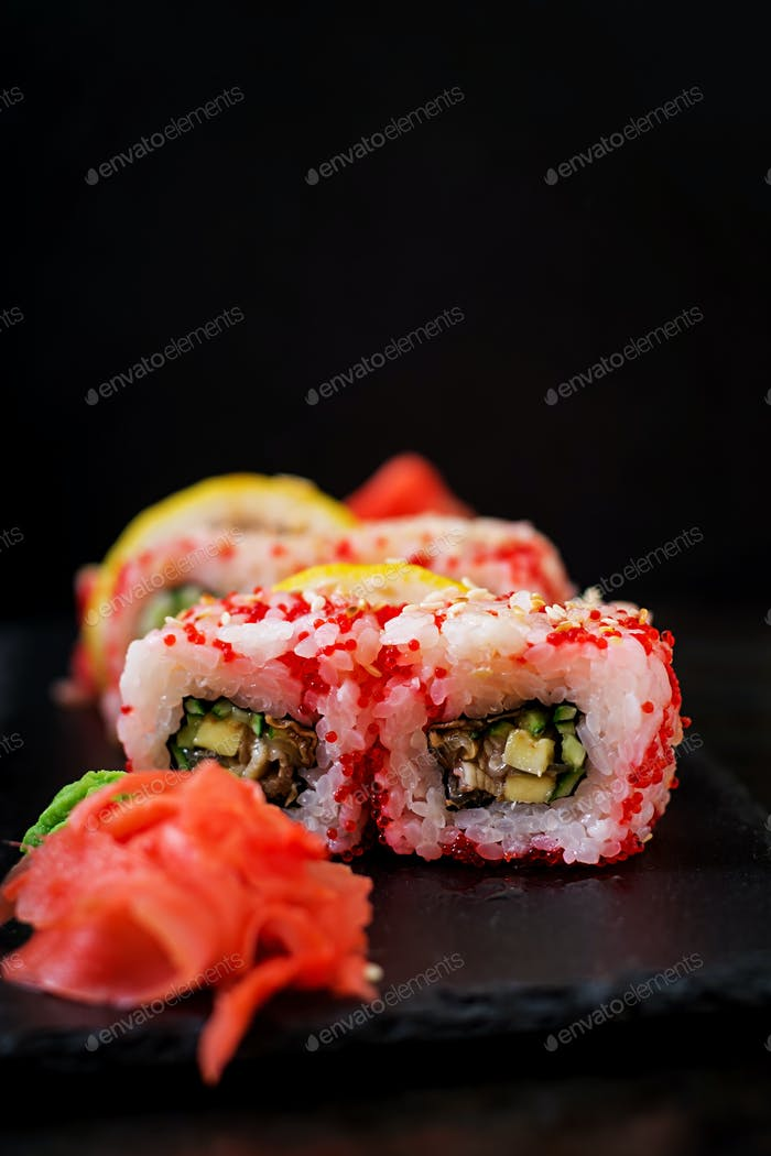 Traditional Japanese food - sushi, rolls and sauce on a black background.
