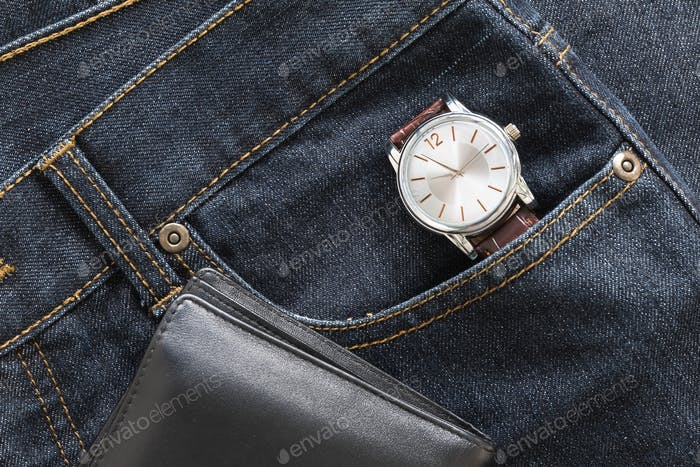 Wristwatch and wallet on denim jeans pocket