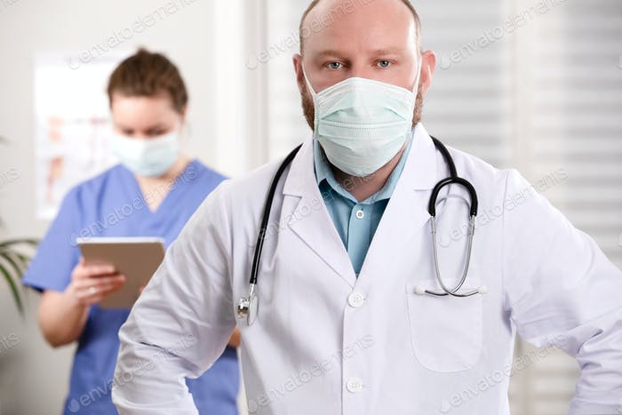 Confident Doctor And Nurse With Arms Crossed In Clinic