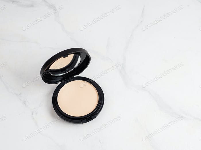 Compact powder on white marble, copy space