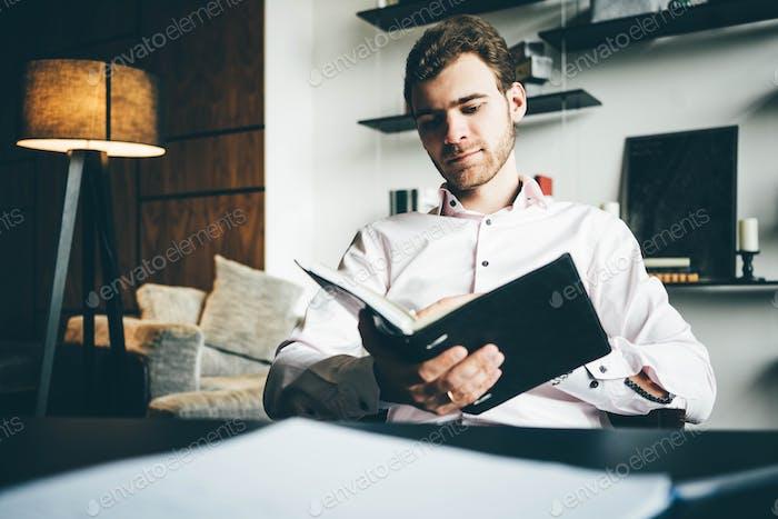 Geschäftsmann beim Lesen von Informationen am Notebook während der Arbeit mit Laptop im Büro