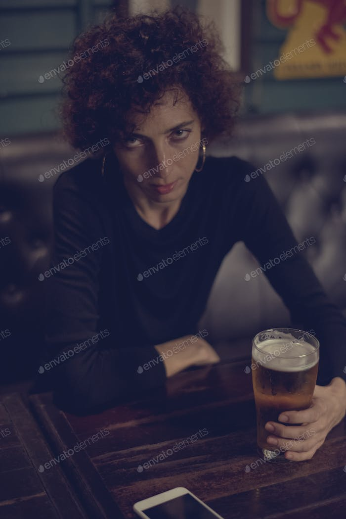 Woman having a beer at a bar