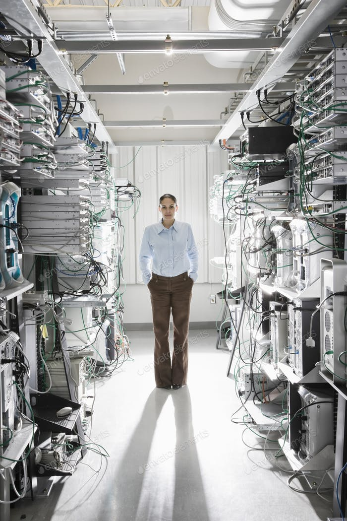 Caucasian woman technician working in the aisle of a computer server farm.
